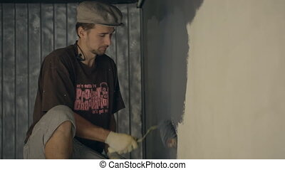 Man in cap carefully paints wall in gray colour He need to...