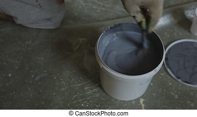 Erector carefully stirs gray paint in plastic pail to apply...