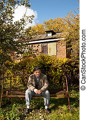 Serious middleaged man sit on old rusty bed in autumnal...