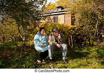 Middleaged man and woman sit on old rusty bed in autumnal...