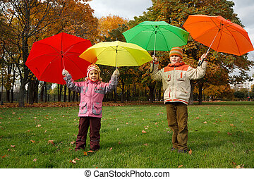 Boy and little girl in autumn park. Hold over heads colour umbrellas.