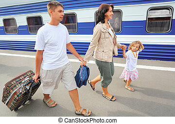 Happy family with little girl going on railway station