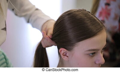 Woman creates hairstyle to her friend in art studio in day...