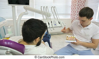 A man with a beard lying in dental chair, next to telling...