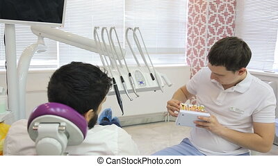 Young male dentist using a tooth model says patient is in...