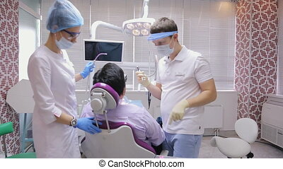 Dentist man in mask with dental tip works at mouth of patient, nurse assists.