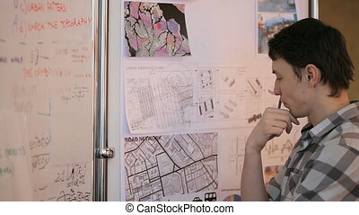 Young professional at urban development considers future areas given for construction, standing next to map and plans of area.