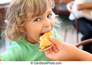 pretty little girl eats hamburger from mothers\'s hand