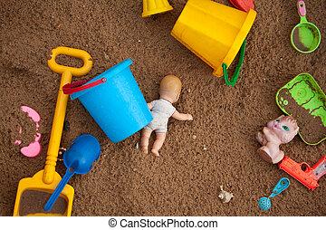 The thrown toys in a sandbox