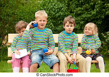 Two boys and two girls on a bench in park In identical...