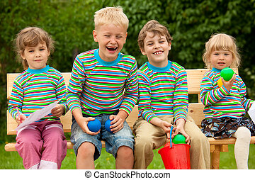 Four children in identical clothes laugh sitting on a bench.