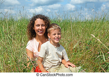young woman and smiling boy sitting on meadow