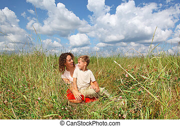 young woman and smiling boy sitting on meadow, Looking...
