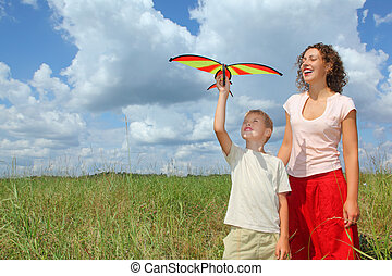 young woman and boy plays kite on meadow