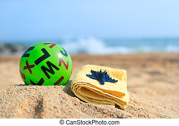 Green bal at the beach - Green toy ball with letters and...
