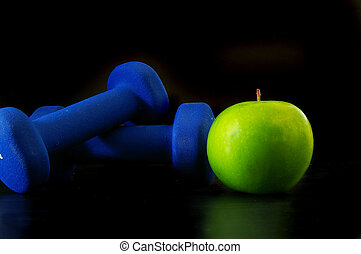 Green apple and two hand weights, on black
