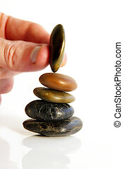 Hand placing a small stone on a stack of three