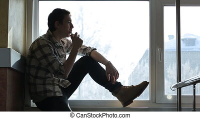Handsome man sits on windowsill and smokes electronic...