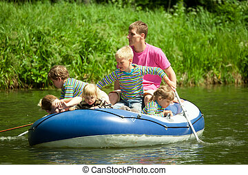Children go for a drive on an inflatable boat under...