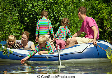 Children and adults float on an inflatable boat
