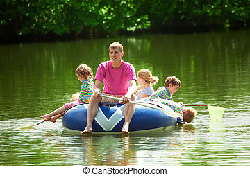 Children and adults float on an inflatable boat in a sunny...