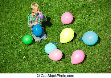 The boy inflates balloons, sitting on a grass