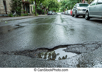 Pothole - Large deep pothole in Montreal street, Canada.