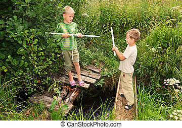 Two boys with sticks battling for fun on bridges over stream