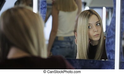 Girl brushes her blond hair sitting beside mirror. She...