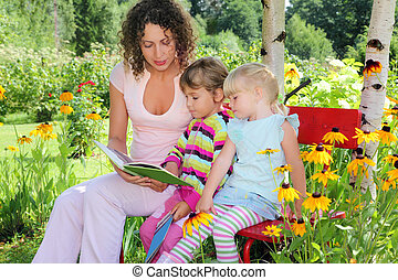 young woman reads the book to two little girls in garden