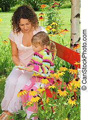 young woman reads the book to little girl in garden