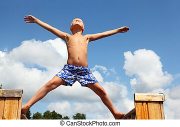 boy in shorts standing on boards against clouds, plants...