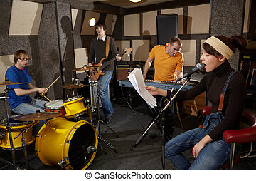 a rock band is working in studio. vocalist girl is singing with text of song in the her hand