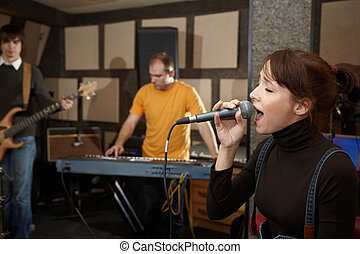vocalist girl is singing. electro guitar player and keyboarder in out of focus