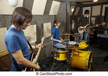 a rock band. two musicians with electro guitars and one drummer working in studio