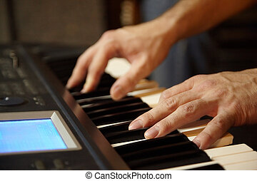 keyboard player playing in studio. hands of keyboard player