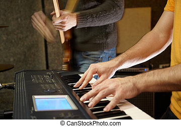 keyboard player playing in studio. guitar player in out of...