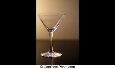 Vermouth cocktail pouring in martini glass with dropping green olive