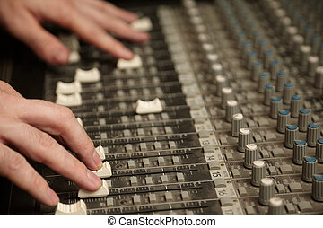 sound producer moving faders of dirty sound mixer pult focus...