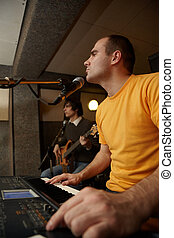keyboarder is playing near microphone. guitar player in out...