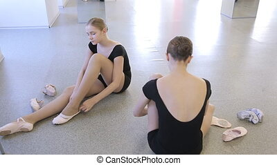 Young girls prepare for ballet lesson in dancing class. They...