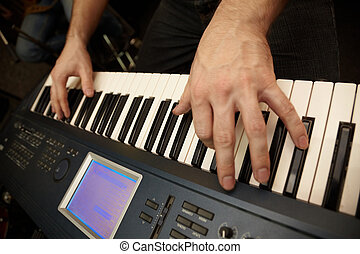 hands of keyboard player on keys of synthesizer focus on big...