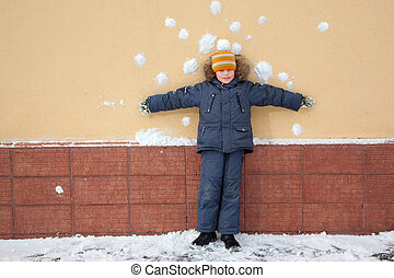 boy kid is standing near wall with snowballs snow stains....