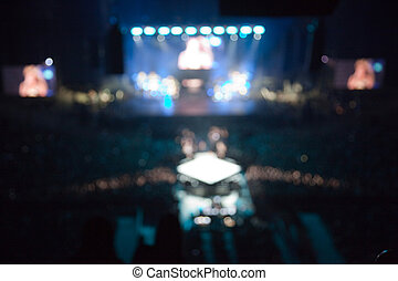 unfocused blurred view. musical performance concert. blue cold tone light show.  bright lights above stage