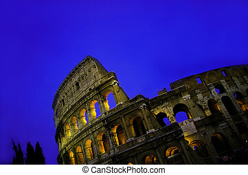 The colosseum  in Rome  at dusk, with blue sky