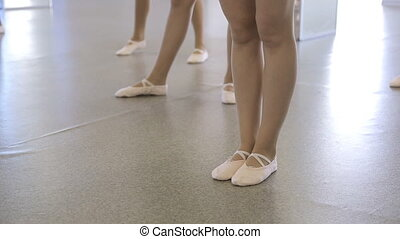 Ballerinas stand on floor which is covered with linoleum....