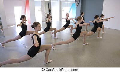 Pretty young girls train in dancing class to develop flexibility.