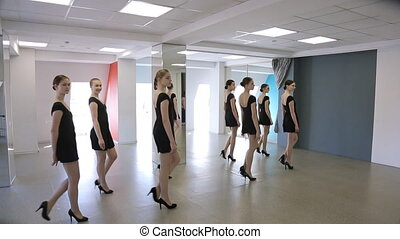 Group of young girls trains defile in classroom in model...