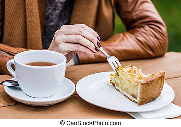 Woman eating bee sting cake, outdoors, grain effect