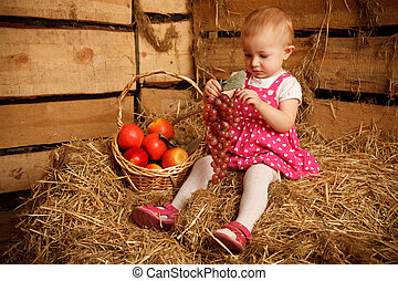 Little girl is sitting on pile of straw with grapes in their hands. Near fruit basket.